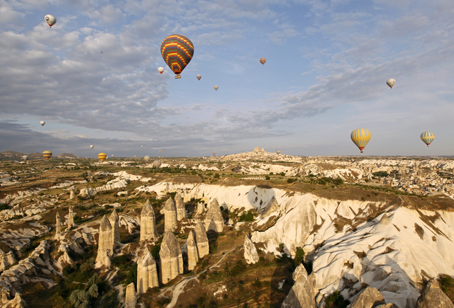 epa03293362 A picture made available on 03 July 2012 shows hot air balloons flying over a valley of the UNESCO World Heritage Rock Cave site of Cappadocia, a region stretching across the south-eastern part of central Anatolia with formations of volcanic tuffs and sandstones carved by erosion, in Turkey 22 June 2012. The number of foreign tourists visiting Turkey declined by 1.53 percent at to 3.23 million in May 2012. The number European tourists has dropped due to the ongoing European debt crisis. EPA/RUNGROJ YONGRIT